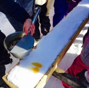 Hot maple syrup taffy is being placed on clean snow