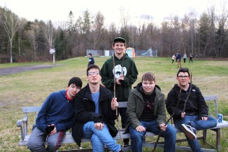 Group of 5 teen boys holding up sticks